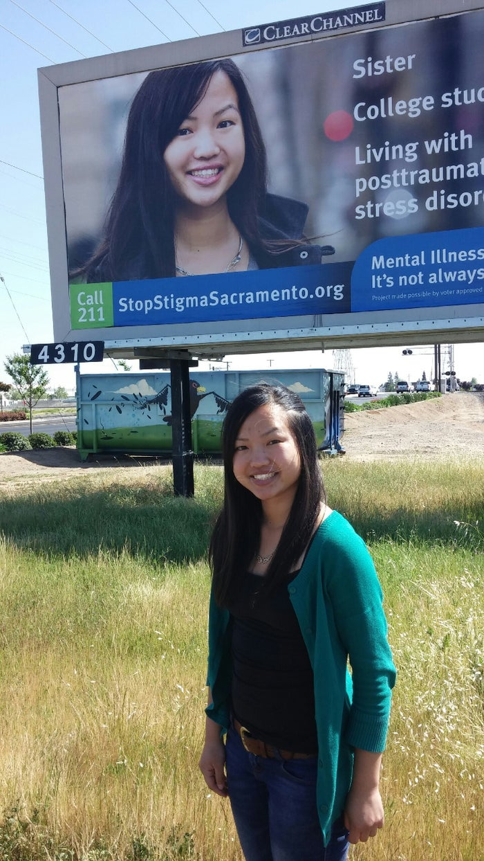 Pangcha Vang in front of one of the billboards.
