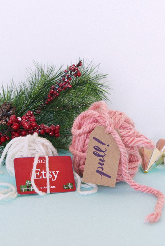 One way to make a gift card more fun to receive is to make it harder to open. For this simple yarn ball project, all you need is an extra skein. Just tie one end of the yarn around the card and continue wrapping until you have a hefty ball. Then add a little tag to the other end of the strand with the instruction: Pull!