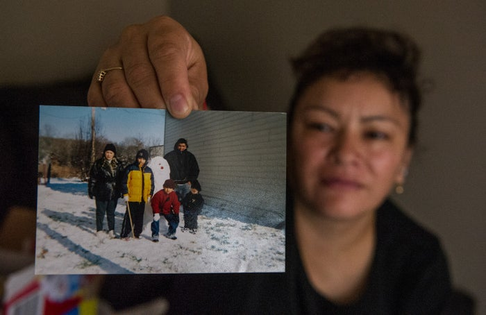 Luis's mother, María Susana, holds up a picture of the family shortly after their arrival in Tennessee.
