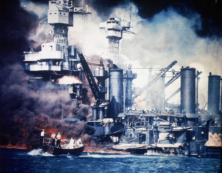 At the scene of the attack, a small boat rescues a USS West Virginia crew member from the water after the Japanese bombing raid.