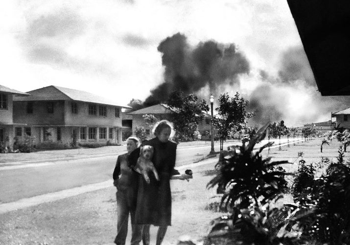 "Officers' wives head to their quarters after hearing explosions and seeing smoke in distance. Mary Naiden, the woman who took this picture, is said to have exclaimed, ""There are red circles on those planes overhead. They are Japanese!"""