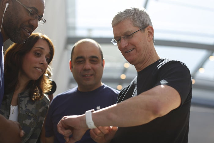 Apple CEO Tim Cook displays his personal Apple Watch to customers at an Apple Store.
