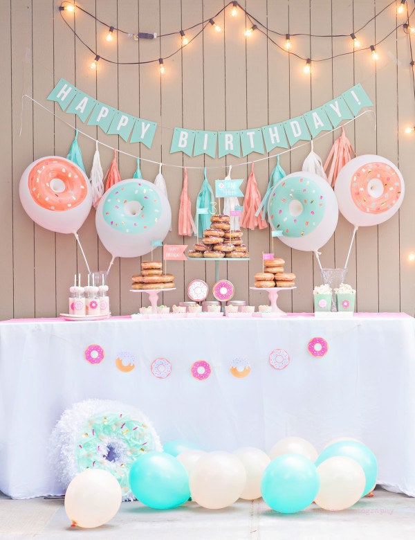 Who doesn't like doughnuts? People who hate joy (and their tastebuds). The people at Fancy That *love* doughnuts and they put together the beauteous mint and coral colored party you see above (photographed by Katie Hickenbottom). You can learn how to make your own doughnut balloons and a doughnut piñata using their simple tutorials.