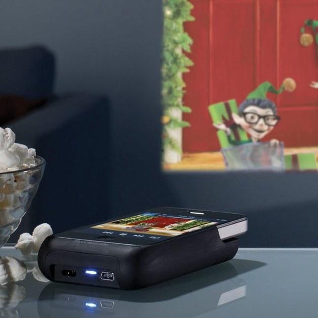 Este proyector de bolsillo ($88) que también carga tu teléfono.
