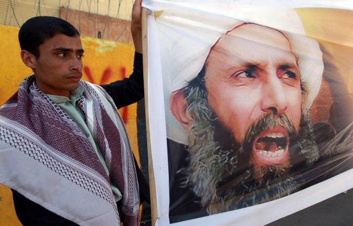 Yemeni protesters hold a photo of Nimr al-Nimr in Sanaa
