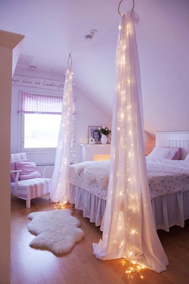 Or thread sheer fabric and string lights through two smaller hoops for instant coziness.