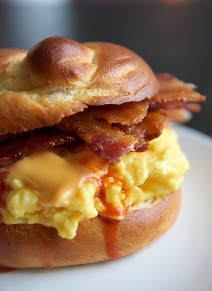 Pile your scrambled eggs high and proud on a toasted kaiser roll or English muffin, top the eggs with a slice of *American Cheese*, some crispy bacon and too much hot sauce.