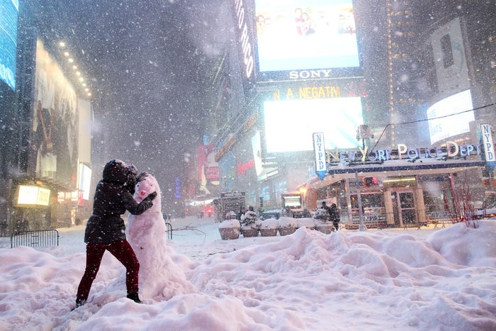A woman decorates a snowman in Times Square Saturday.