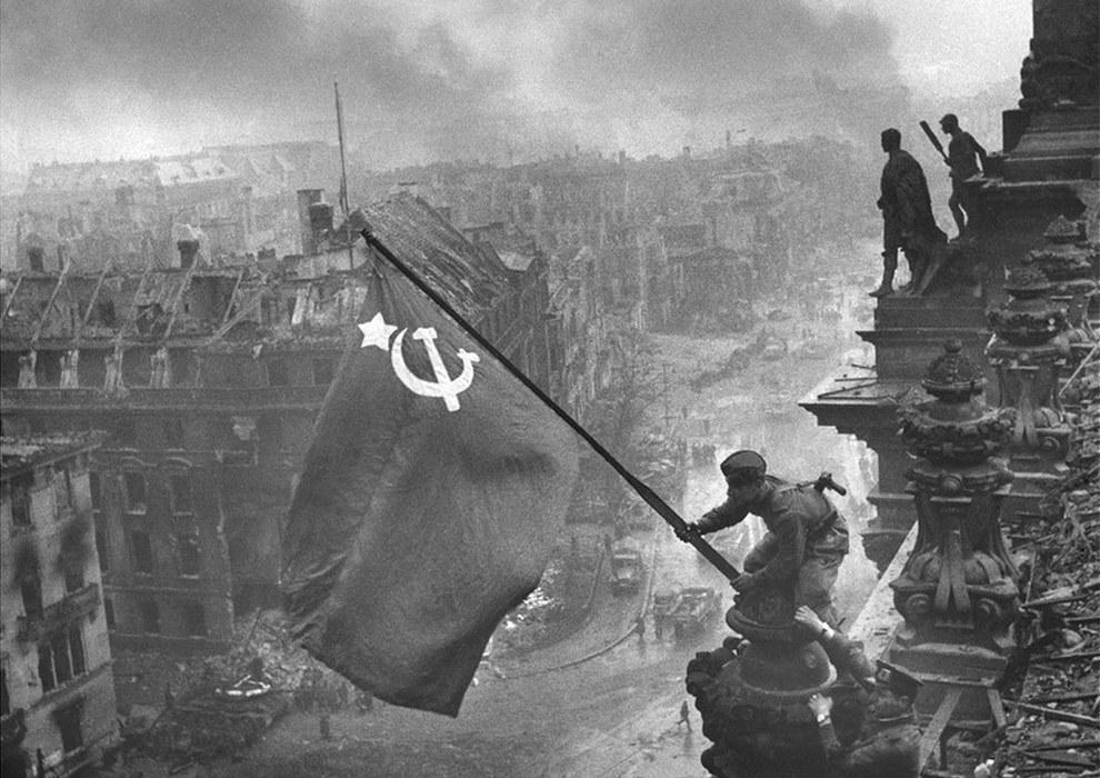 Soldados del Red Army izando una bandera de la hoz y el martillo sobre Reichstag en Berlín, 1945.