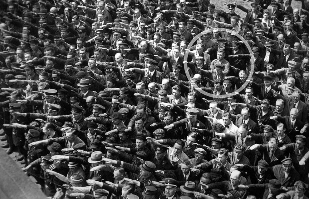 August Landmesser negándose a hacer el saludo Nazi en un mitin multitudinario.