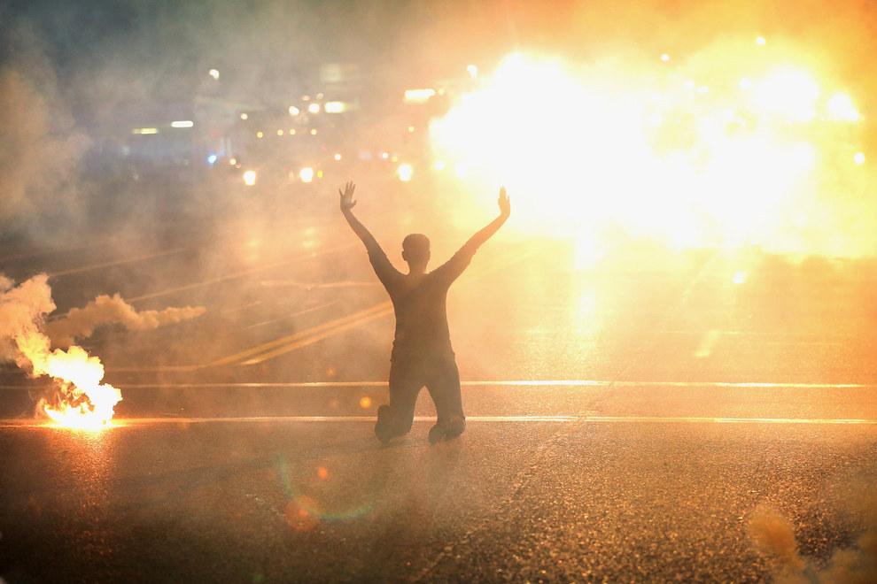 Esta mujer en Ferguson, Missouri, demostrándose de rodillas entre una nube de gas lacrimógeno en el 2014.