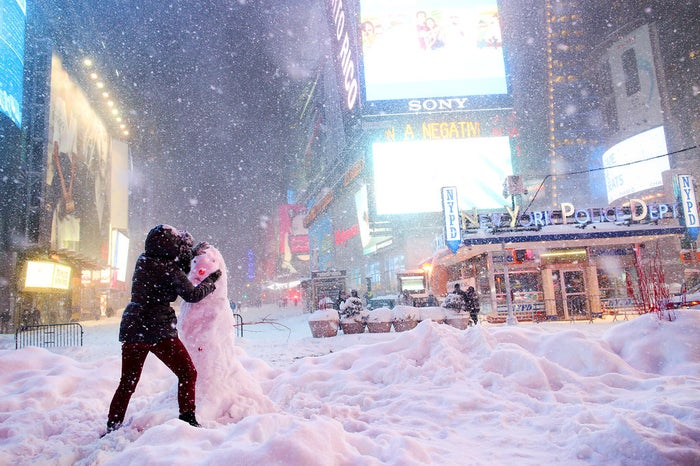 A woman decorates a snowman in Times Square on Jan. 23 in New York City. Last weekend, the Northeast and parts of the South experienced heavy snow and ice from a slow-moving winter storm.