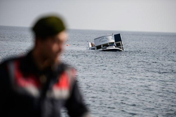 Turkish coastguard officials work near the scene of the sinking boat on Saturday.