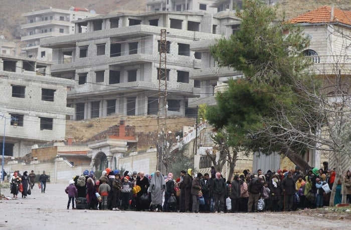 Madaya residents wait for a convoy of aid from the Syrian Arab Red Crescent to arrive.