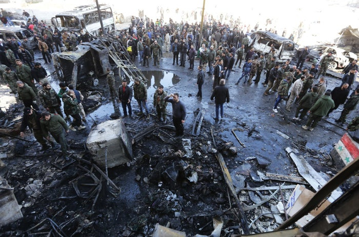 People gather at the site of the blast on Sunday.