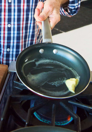 Put the skillet over medium heat and add about 2 tablespoons of that butter. The butter should sizzle a little, but not furiously. It should melt quickly.
