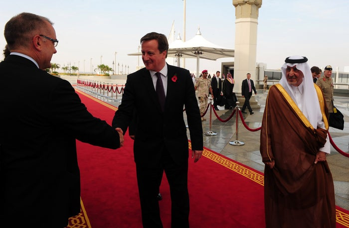 An unidentified official greets David Cameron as he walks with Prince Khalid bin Faisal bin Abdulaziz (right) upon arrival in Jeddah on 6 November 2012.