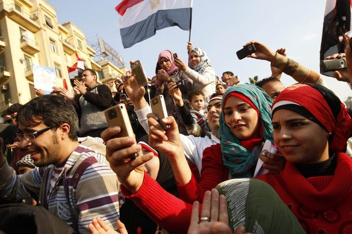 Egyptians use cell phones in Cairo's Tahrir Square during the protests that drove longtime leader Hosni Mubarak from power, Feb. 12, 2011.
