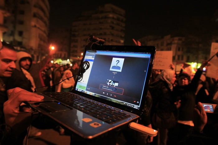 An Egyptian protester streams a demonstration via Skype as people gather in Cairo's Tahrir Square.