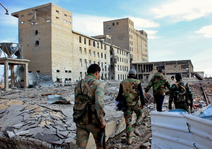Syrian army soldiers patrol near a building previously used for storing seeds in the countryside of Deir Hafer.