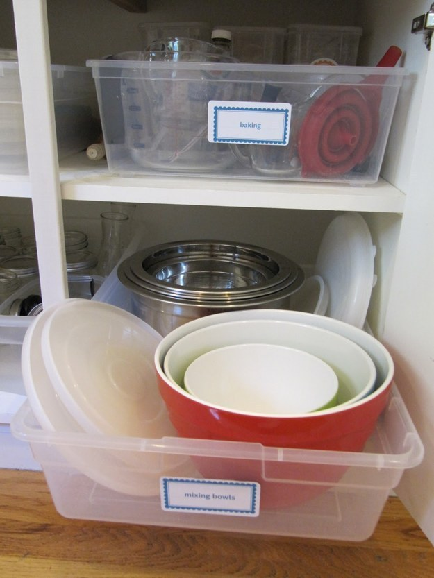 Pick your messiest kitchen cabinet, and use inexpensive plastic bins as faux pull-out drawers.