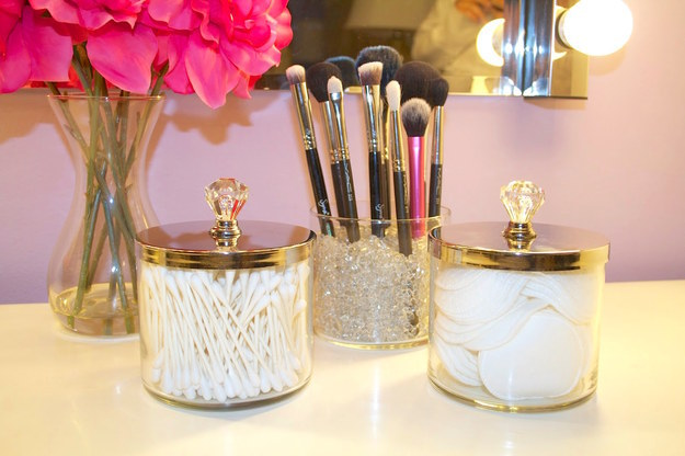 Freeze old candles to get rid of the excess wax, then turn the empty jars into pretty containers for your vanity.
