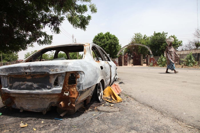 A woman walks by a burned-out car in Michika