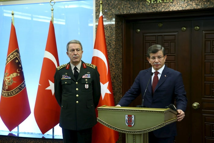Turkish Prime Minister Ahmet Davutoglu, flanked by Chief of Staff General Hulusi Akar (left), at the Army headquarters in Ankara, Feb. 18.