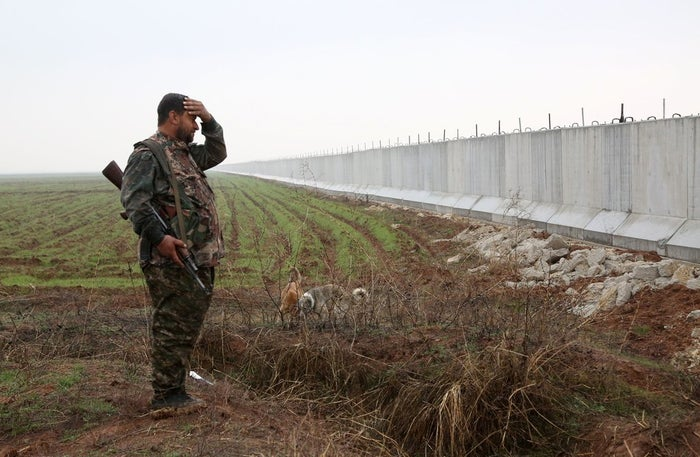 A YPG fighter stands near a wall on the Syria-Turkey border.