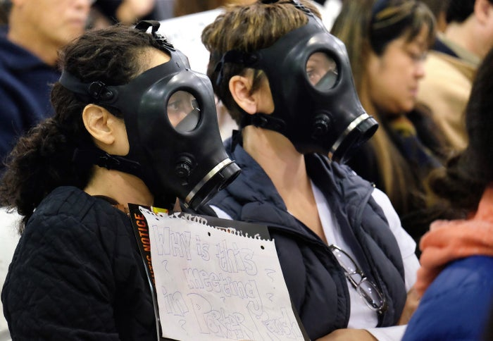 Wearing gas masks, protestors attend a hearing over the gas leak.