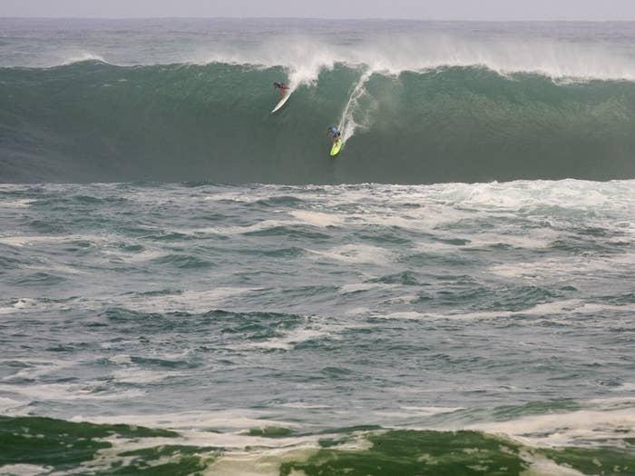 Jamie Mitchell, right, and Ross Clarke-Jones, both of Australia, surf in the Eddie.