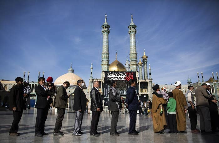 Iranians line up to vote in Qom on Friday.
