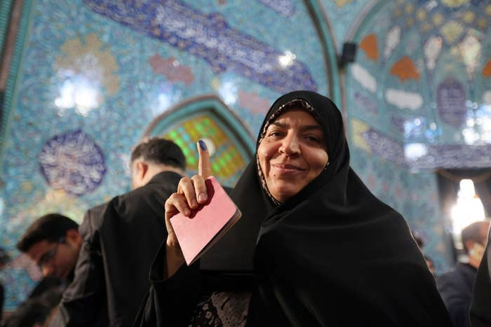 An Iranian woman displays her ink-stained finger after casting her ballot in Tehran.