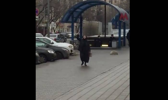 A screengrab of a video purporting to show the woman holding the severed head outside the Moscow subway station on Feb. 29, pixelated by BuzzFeed News.