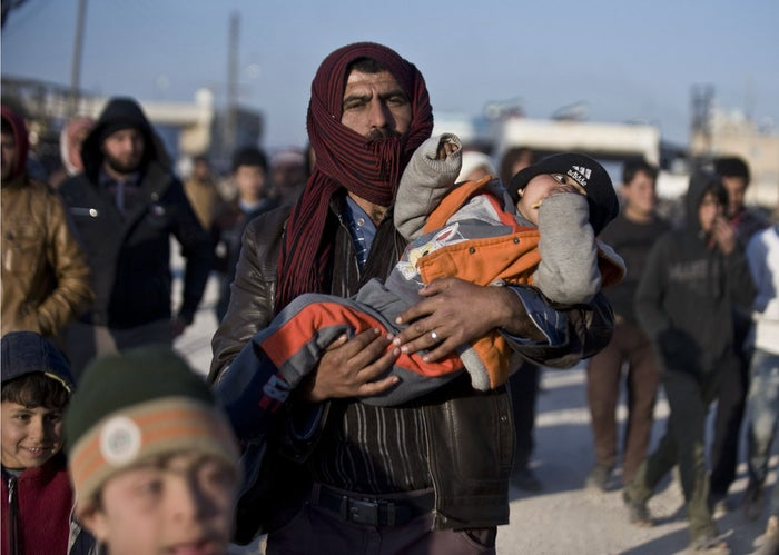 Syrians walk towards the Turkish border at the Bab al-Salam border gate, Syria