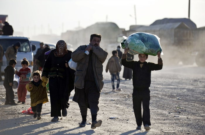 Syrians walk towards the Turkish border at the Bab al-Salam border gate