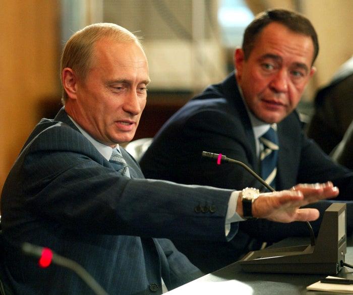 Russian President Vladimir Putin gestures as then-Mass Media MinisterMikhail Lesin listens in 2002