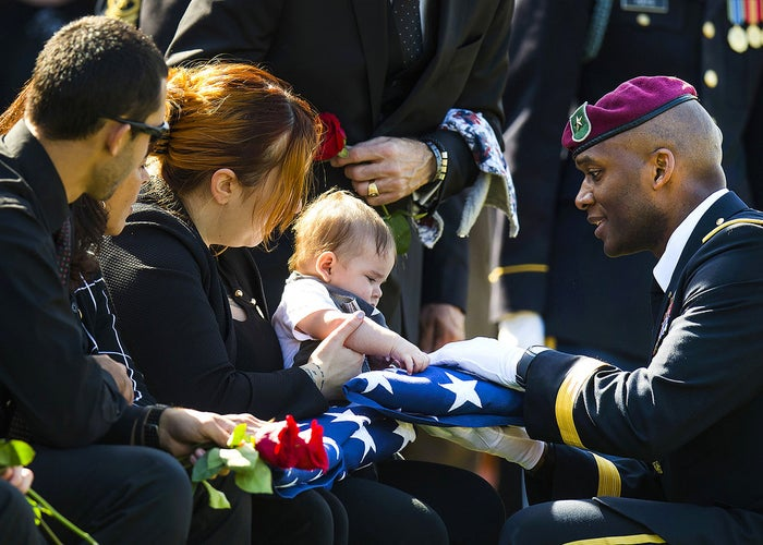 Widow Alexandra McClintock holds an American flag with her son Declan during the burial of her husband, U.S. Army Sgt. 1st class Matthew McClintock, at Arlington National Cemetery in Arlington, Virginia. McClintock, a Special Forces engineer sergeant, was killed on January 5th while conducting operations in southern Afghanistan.