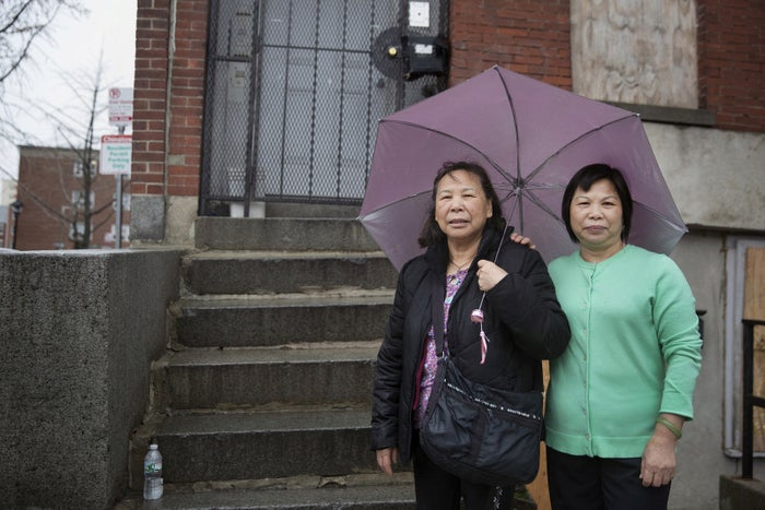 The two sisters stand in front of their old apartment building.