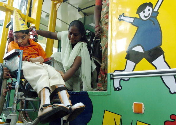 """An assistant helps a disabled boy embark Chennai's """"Fun Bus,"""" which takes underprivileged children on citywide tours."""