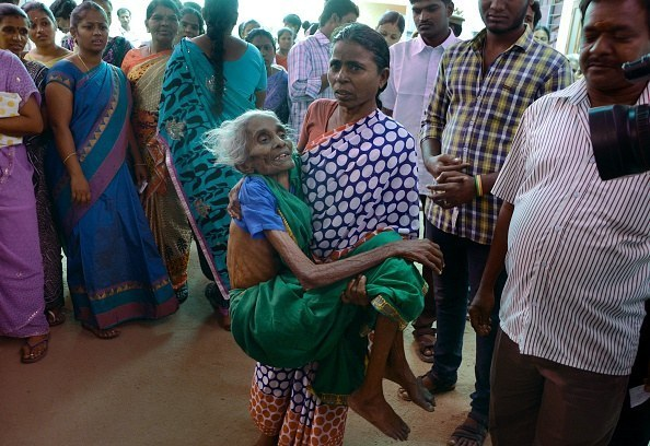 One Chennai resident carries another to a polling station so she can cast her vote.