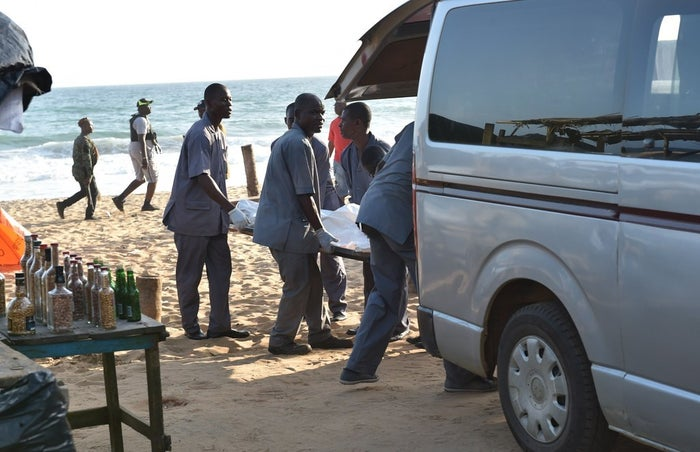 A body is placed into a van on the beach in Grand-Bassam.