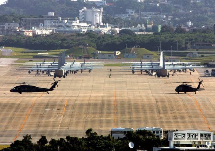 Marine Corps helicopters and transport planes are seen on a tarmac in Okinawa.