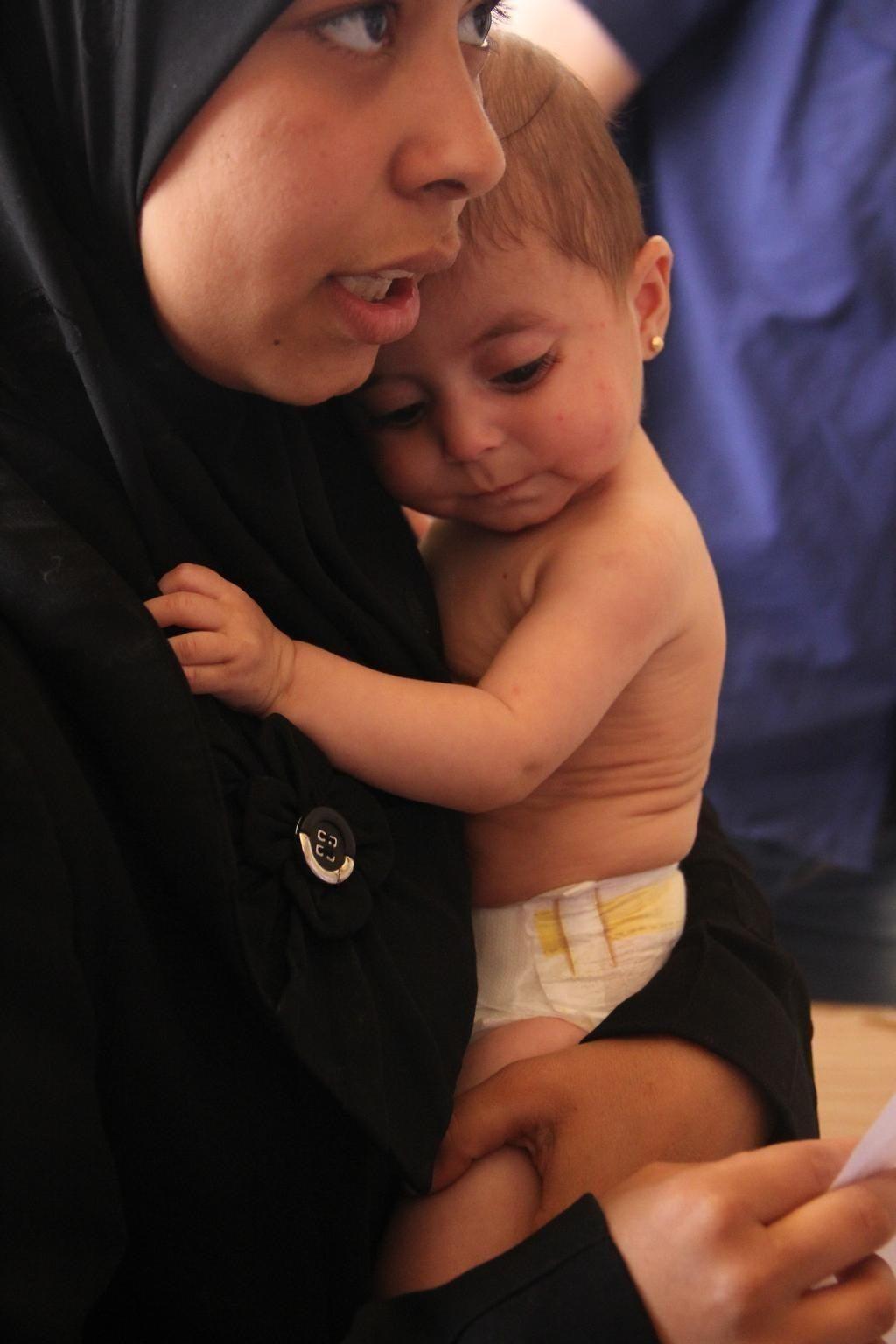 2014年6月11日シリア・アラブ共和国で女性が幼い娘を抱きかかえている。娘はアレッポ県の中心都市アレッポの、ユニセフが支援する医療センターで栄養失調の治療を受けた。