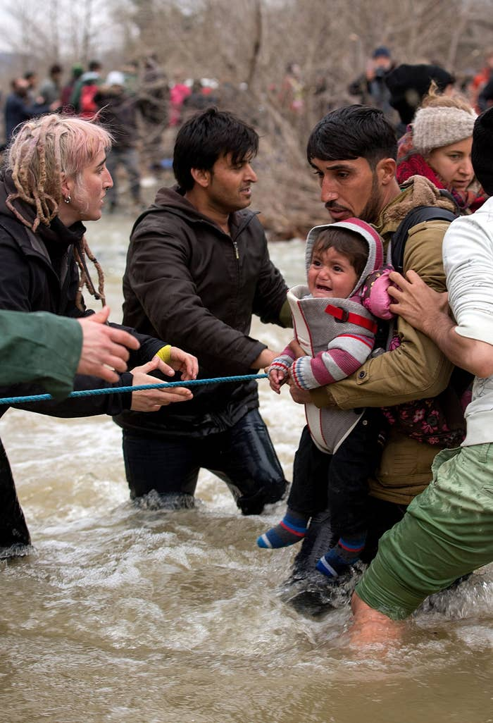 Refugees ford a swollen river after leaving the Idomeni refugee camp in a desperate bid to reach Macedonia.