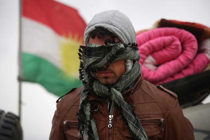 A suspected ISIS fighter is detained by Kurdish Peshmerga forces.