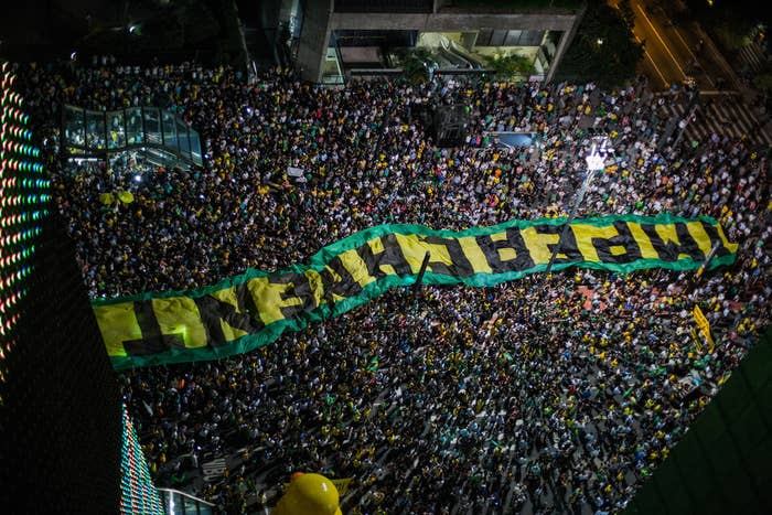 "A banner reading ""impeachment"" is carried across one of São Paulo's avenues."
