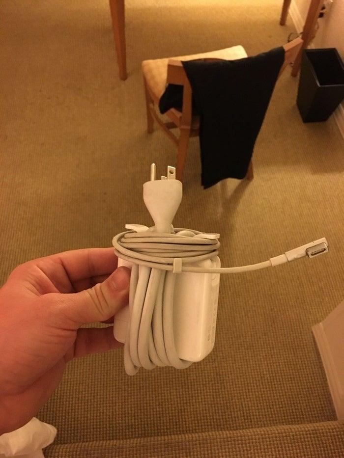 Si vous enroulez la partie large en premier, après vous pouvez la maintenir en place en enroulant le cordon plus fin sous les ailes de l'adaptateur. Puis vous utilisez le clip pour fixer le bout du cordon. Le tour est joué!