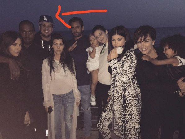 No, it's not Kanye West giving his best attempt at a smile. And no, it's not the fact that Scott's there. Look — there's Rob!