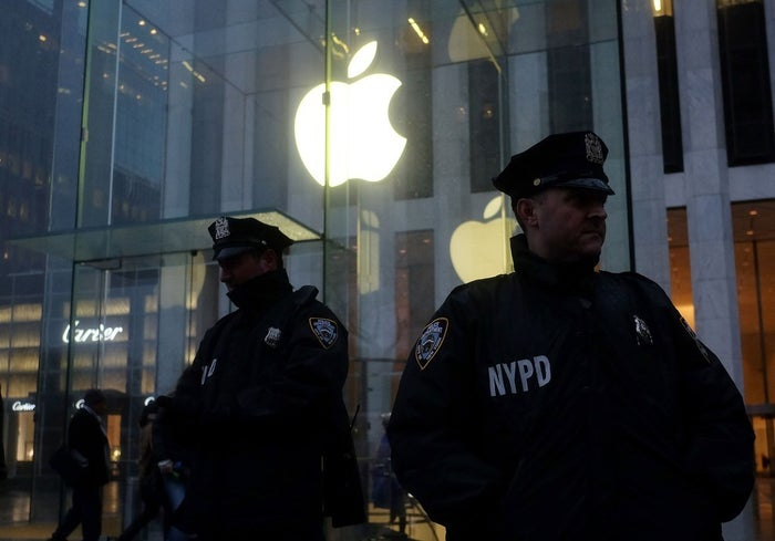 Two New York Police Department (NYPD) officers stand gaurd during a demonstration outside the Apple store on Fifth Avenue in New York on February 23, 2016.